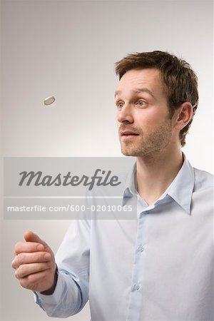 Man Flipping Coin Stock Photo - Premium Royalty-Free, Image code: 600-02010065