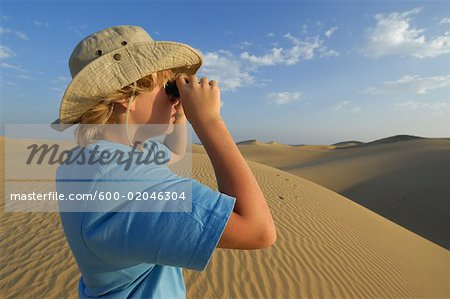 Boy Looking Out Over Sand Dunes Through Binoculars, Playa del Ingles, Cran Canaria, Canary Islands Stock Photo - Premium Royalty-Free, Image code: 600-02046304