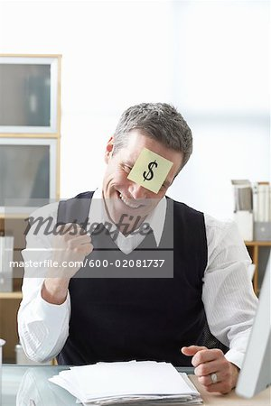 Businessman Sitting at Desk with Self Adhesive Note on Forehead Stock Photo - Premium Royalty-Free, Image code: 600-02081737