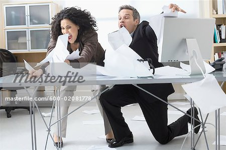 Business People Trying to Hold onto Paperwork Blowing Around on Desk Stock Photo - Premium Royalty-Free, Image code: 600-02081778