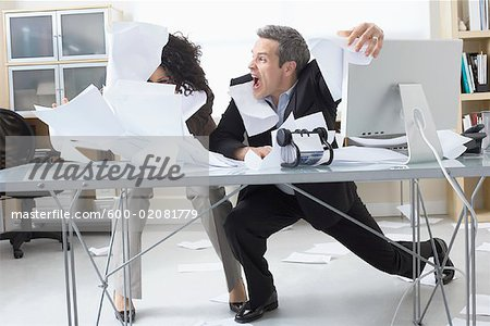 Business People Trying to Hold onto Paperwork Blowing Around on Desk Stock Photo - Premium Royalty-Free, Image code: 600-02081779