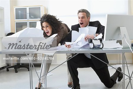 Business People Trying to Hold onto Paperwork Blowing Around on Desk Stock Photo - Premium Royalty-Free, Image code: 600-02081784