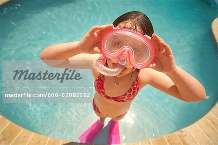Girl Wearing Snorkel and Goggles in Swimming Pool Stock Photo - Premium Royalty-Free, Image code: 600-02082092