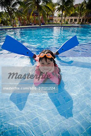 Girl Lying in Swimming Pool Wearing Goggles and Flippers Stock Photo - Premium Royalty-Free, Image code: 600-02121224