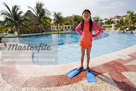 Girl Standing with Hands on Hips Next to Swimming Pool Stock Photo - Premium Royalty-Free, Image code: 600-02121226