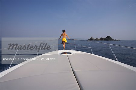 Woman Standing on Bow of Yacht, Girolata Marine Park, Corsica, France Stock Photo - Premium Royalty-Free, Image code: 600-02130722