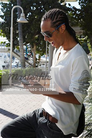 Young Man Sending a Text Message Stock Photo - Premium Royalty-Free, Image code: 600-02199794