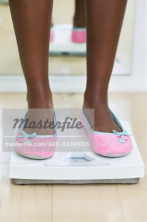 Woman's Feet on Bathroom Scale Stock Photo - Premium Royalty-Free, Image code: 600-02245725