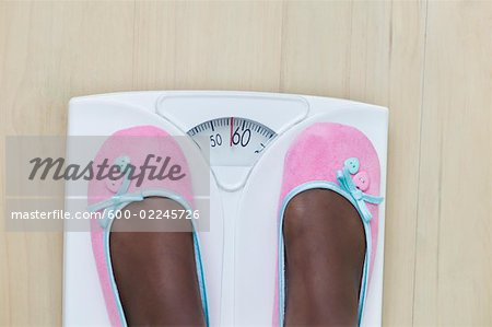 Woman's Feet on Bathroom Scale Stock Photo - Premium Royalty-Free, Image code: 600-02245726