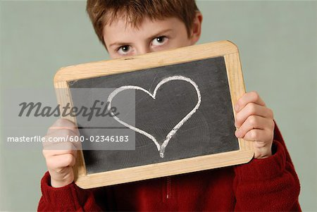 Boy Holding Chalkboard with Heart Drawn on It Stock Photo - Premium Royalty-Free, Image code: 600-02346183
