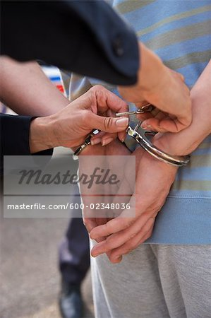 Close-up of Police Officer Handcuffing Suspect Stock Photo - Premium Royalty-Free, Image code: 600-02348036