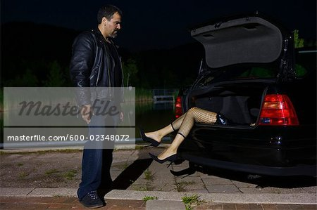Man Looking at Dead Body in Trunk of Car