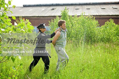 Police Officer Arresting Suspect Stock Photo - Premium Royalty-Free, Image code: 600-02348148