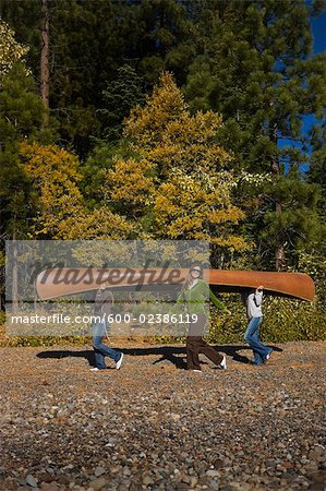 Three Women Carrying Canoe in the Forest Stock Photo - Premium Royalty-Free, Image code: 600-02386119