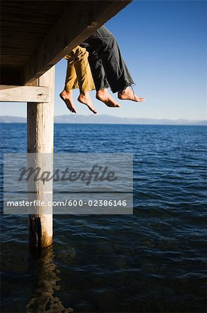 Women Dangling Feet from Dock over Lake Stock Photo - Premium Royalty-Free, Image code: 600-02386146