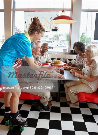 Waitress Serving Customers in Retro Diner Stock Photo - Premium Royalty-Free, Image code: 600-02429044