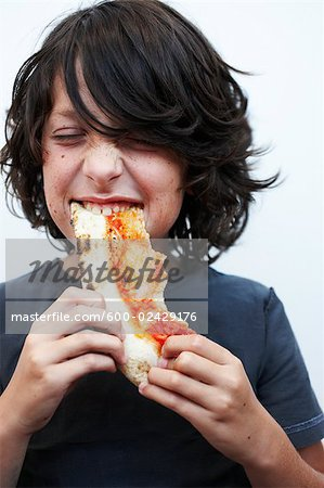 Boy Eating Pizza Stock Photo - Premium Royalty-Free, Image code: 600-02429176
