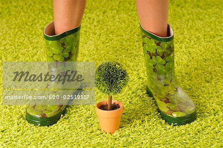 Woman in Rubber Boots with Potted Plant Stock Photo - Premium Royalty-Free, Image code: 600-02519117