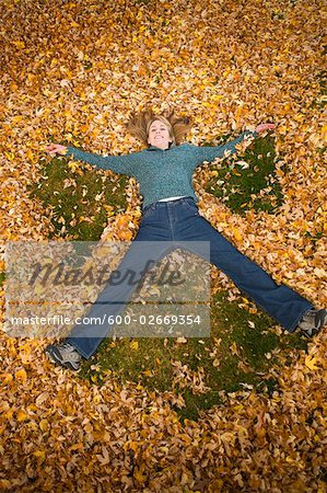 Woman Playing in Leaves in Autumn, Bend, Oregon, USA Stock Photo - Premium Royalty-Free, Image code: 600-02669354