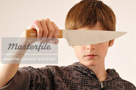 Boy Holding Knife in Front of Eyes Stock Photo - Premium Royalty-Free, Image code: 600-02670199
