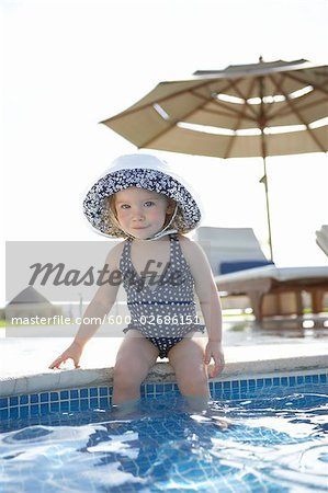 Girl Wearing Bathing Suit and Sunhat, sitting on Edge of Swimming Pool, Cancun, Mexico Stock Photo - Premium Royalty-Free, Image code: 600-02686151