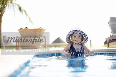 Girl Wearing Sunhat Standing in Swimming Pool, Cancun, Mexico Stock Photo - Premium Royalty-Free, Image code: 600-02686152