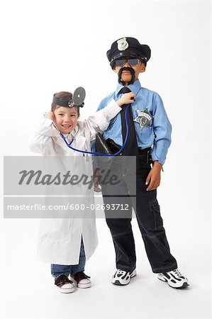 Girl Dressed as Doctor Checking Boy Dressed as Police Officer Stock Photo - Premium Royalty-Free, Image code: 600-02693712