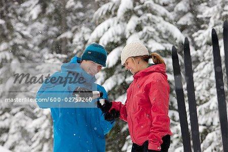 Close-up of Couple Drinking from Thermos, Cross Country Skiing, Whistler, British Columbia, Canada Stock Photo - Premium Royalty-Free, Image code: 600-02757260