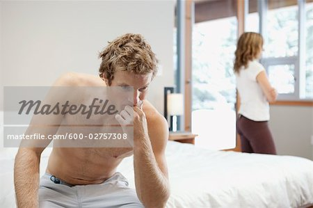 Man Sitting on Edge of Bed and Woman looking out Window in Background Stock Photo - Premium Royalty-Free, Image code: 600-02757308