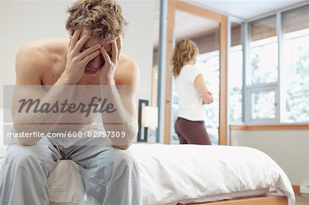 Man Sitting on Edge of Bed and Woman looking out Window in Background Stock Photo - Premium Royalty-Free, Image code: 600-02757309
