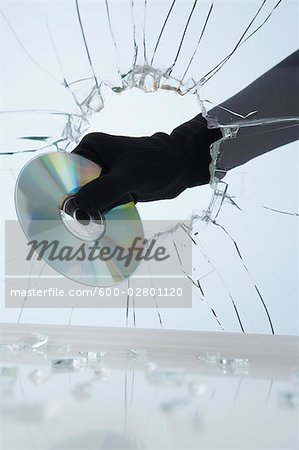 Hand Stealing CD Through Broken Glass Stock Photo - Premium Royalty-Free, Image code: 600-02801120