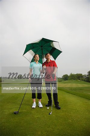 Father and Daughter on the Golf Course Holding a Large Umbrella Stock Photo - Premium Royalty-Free, Image code: 600-02883090