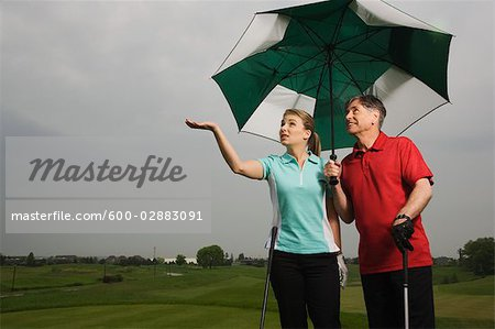 Father and Daughter on the Golf Course Holding a Large Umbrella Stock Photo - Premium Royalty-Free, Image code: 600-02883091