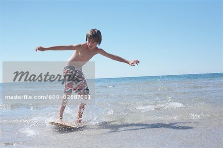 Boy Skimboarding at Deanlea Beach, Elmvale, Ontario, Canada Stock Photo - Premium Royalty-Free, Image code: 600-02887091