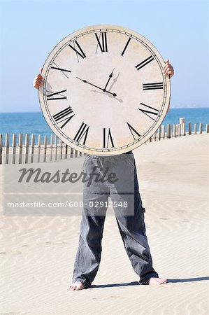 Boy Holding a Large Clock on the Beach Stock Photo - Premium Royalty-Free, Image code: 600-02912548