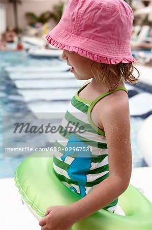 Little Girl With Inner Tube Playing on Pool Deck Stock Photo - Premium Royalty-Free, Image code: 600-02967521
