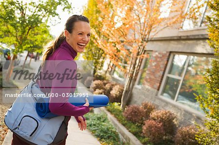 Woman Walking and Carrying Yoga Mat, Seattle, Washington, USA Stock Photo - Premium Royalty-Free, Image code: 600-03017951