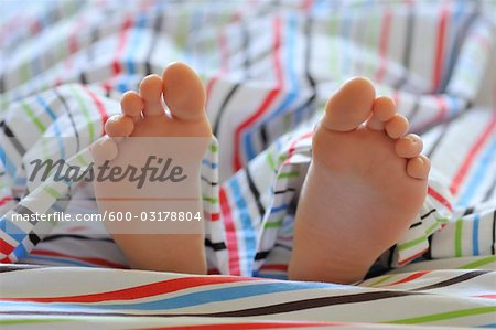 Close-up of Child's Feet in Bed Stock Photo - Premium Royalty-Free, Image code: 600-03178804