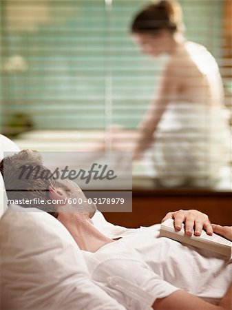 Man Lying in Bed Watching Woman Getting Ready to Take a Bath Stock Photo - Premium Royalty-Free, Image code: 600-03178979