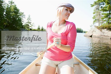 Woman Canoeing on Kahshe Lake, Muskoka, Ontario, Canada Stock Photo - Premium Royalty-Free, Image code: 600-03195044