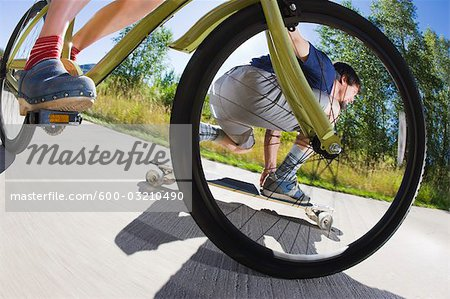 Woman Riding a Bicycle and Man Riding a Skateboard on a Bike Path, Steamboat Springs, Routt County, Colorado, USA Stock Photo - Premium Royalty-Free, Image code: 600-03210490