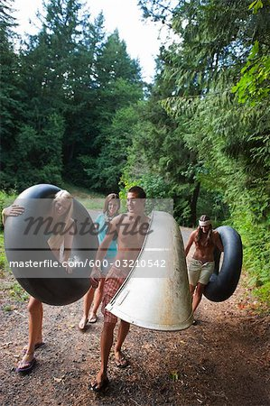 Teenagers Carrying Inner Tubes and a Canoe to the Lake, Near Portland, Oregon, USA Stock Photo - Premium Royalty-Free, Image code: 600-03210542