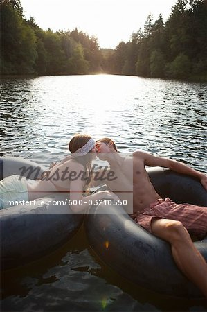 Young Couple Floating on Inner Tubes on the Lake, Near Portland, Oregon, USA Stock Photo - Premium Royalty-Free, Image code: 600-03210550