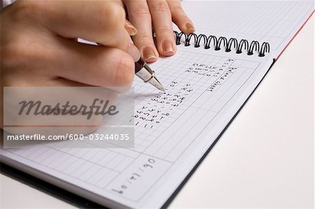 Close-up of Woman's Hands Writing in Book Stock Photo - Premium Royalty-Free, Image code: 600-03244035