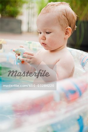 Baby Girl in Inflatable Pool Stock Photo - Premium Royalty-Free, Image code: 600-03284220
