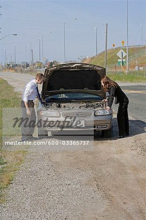 Man and Woman With Car Trouble Looking Under the Hood Stock Photo - Premium Royalty-Free, Image code: 600-03365737