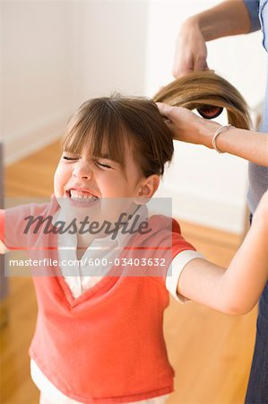 Girl Unhappy with having Hair Brushed Stock Photo - Premium Royalty-Free, Image code: 600-03403632