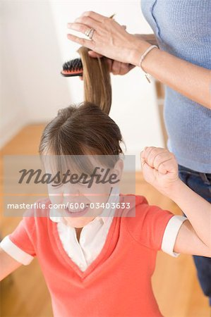 Girl Unhappy with having Hair Brushed Stock Photo - Premium Royalty-Free, Image code: 600-03403633