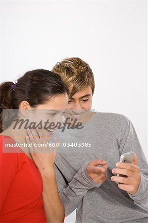 Teenage Girl and Boy with Cell Phone Stock Photo - Premium Royalty-Free, Image code: 600-03403985