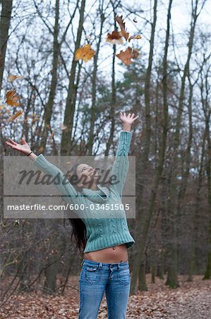 Woman Throwing Autumn Leaves in the Air Stock Photo - Premium Royalty-Free, Image code: 600-03451505